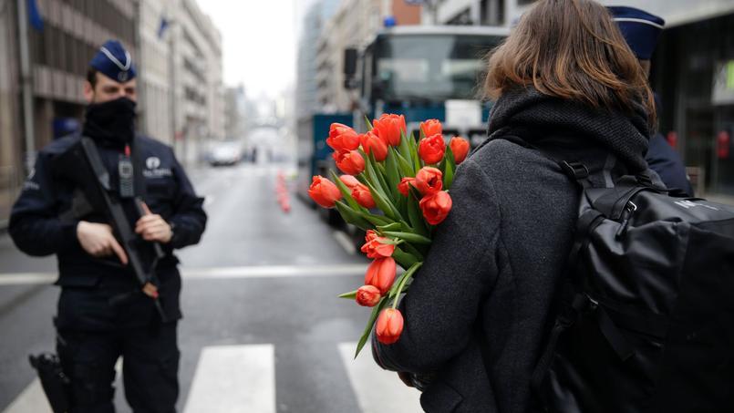 Une femme porte un bouquet de fleurs, dans le quartier de Maelbeek.