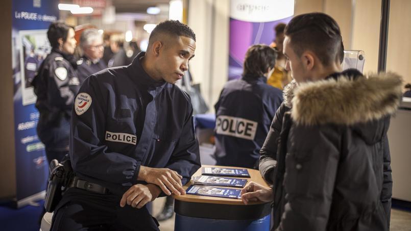 Un jeune homme interroge un policier sur le stand de recrutement de la police nationale, au Salon de l'étudiant, Porte de Versailles, à Paris, en février 2016.