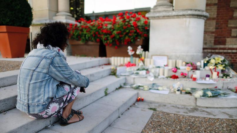 Une femme se recueille devant la mairie de la ville.