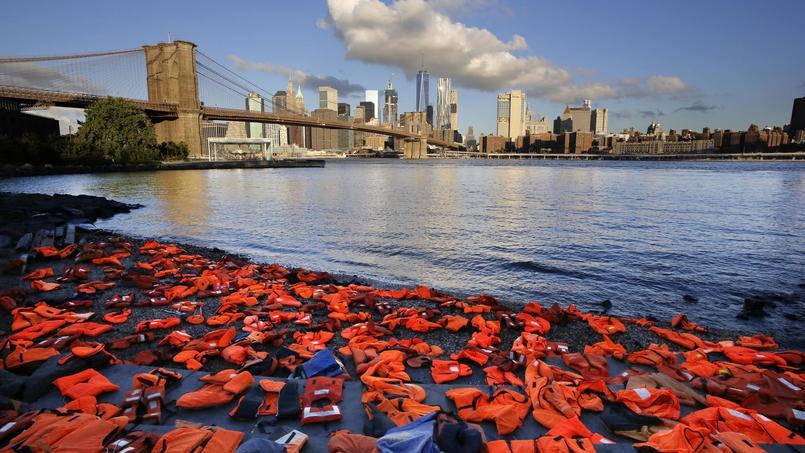 La plage du Brooklyn Bridge Park a été recouverte de gilets de sauvetage, vendredi, faisant ainsi écho aux plages grecques qui prennent régulièrement le même aspect lors de l'arrivée de réfugiés sur les côtes méditerranéennes.