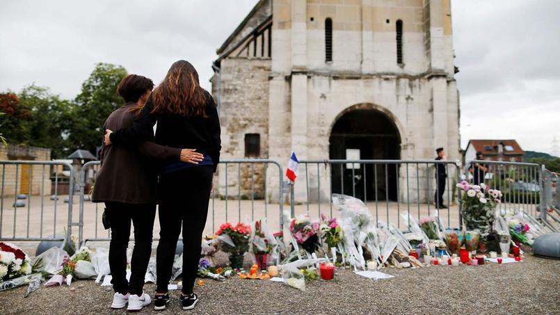 Deux passantes se recueillent devant l'église de Saint-Etienne-du-Rouvray, après l'assassinat du père Jacques Hamel le 26 juillet 2016.