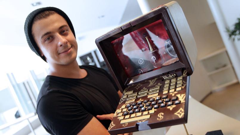 L'artiste Anthony Alberti pose avec son oeuvre «Virtual Love» le 30 juin 2012 pendant une exposition où 30 artistes avaient réalisé des oeuvres d'art à partir de Minitels dans le cadre d'une vente aux enchères (AFP PHOTO/ Valéry Hache)