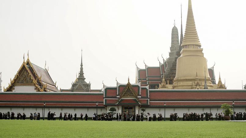 Habillés de noir et de blanc, les Thaïlandais affluent au Grand Palais de Bangkok, où est ouvert le livre des condoléances.