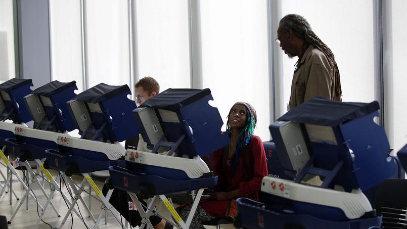 Un assesseur explique à une femme le fonctionnement des machines à voter électroniques, le 31 octobre au Truman College à Chicago.
