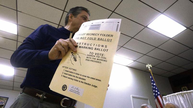 Un électeur de l'Illinois s'apprête à déposer un bulletin de vote. Les formulaires utilisés permettaient de voter sur plusieurs sujets dans de nombreux États.