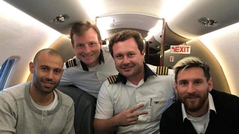 Javier Mascherano (à gauche) et Lionel Messi (à droite) en compagnie des membres de l'équipage d'un avion.