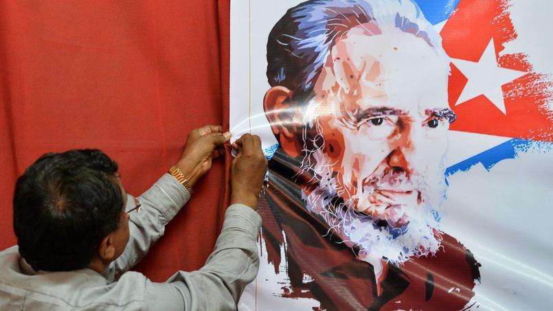 Un membre du parti communiste Indien accroche une image de l'ancien président cubain Fidel Castro.