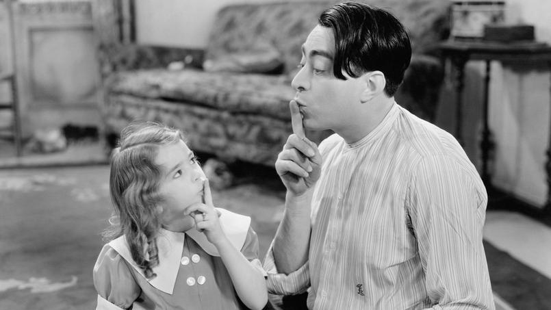 Un homme fait signe à une enfant de faire silence.