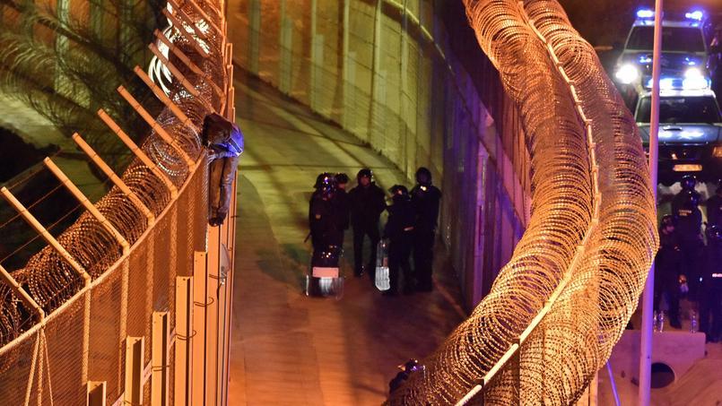 Un migrant s'accroche à l'une des deux clôtures qui sépare le Maroc de Ceuta, dimanche.