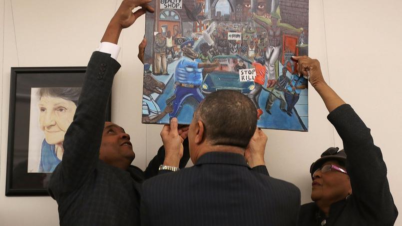 Des membres du Parti démocrate siégeant au Congrès raccrochent le tableau après qu'il a été décroché des murs du Capitole par les Républicains.