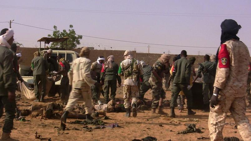 Des hommes procèdent à l'évacuation des corps des victimes de l'attentat, mercredi, à Gao.