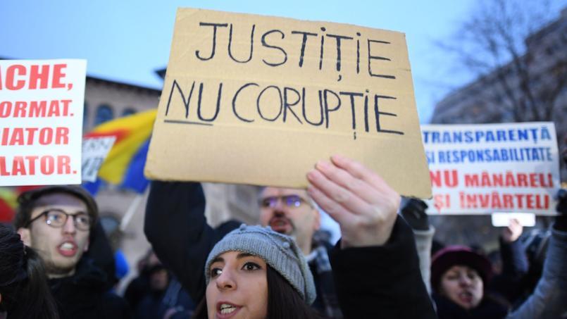Une femme tenant une pancarte «Justice, pas de corruption» durant une manifestation contre la corruption du gouvernement de Bucarest le 22 janvier 2017.