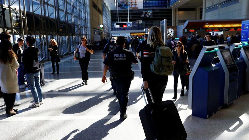 É l'aéroport de Los Angeles, des officiers de la police aux frontières passent de comptoir en comptoir pour prévenir les passagers des nouvelles règles en vigueur.