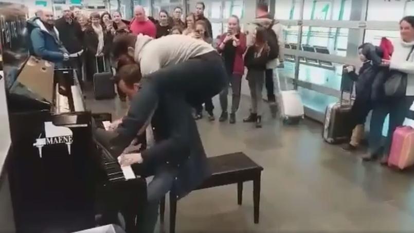 Bartlomiej Szopinski, accompagné de son partenaire des Boogie Boys, joue sur l'un des pianos en libre-service de l'aéroport de Charleroi.