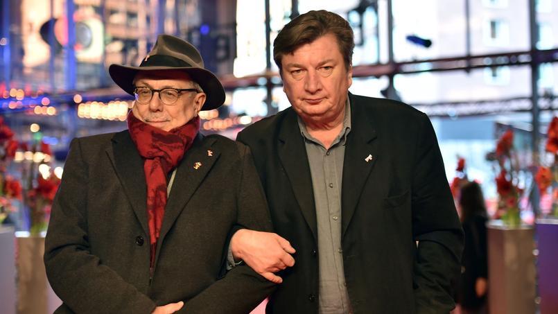 Le réalisateur finlandais Aki Kaurismäki arrive à la première de son film hilarant, On the Other Side of Hope, au bras du directeur de la Berlinale, Dieter Kosslick.