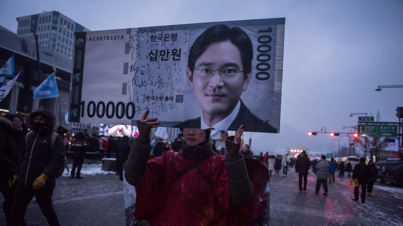 Un manifestant brandit une pancarte montrant le visage de Lee Jae-Yong, lors d'une marche anti-gouvernement à Seoul.