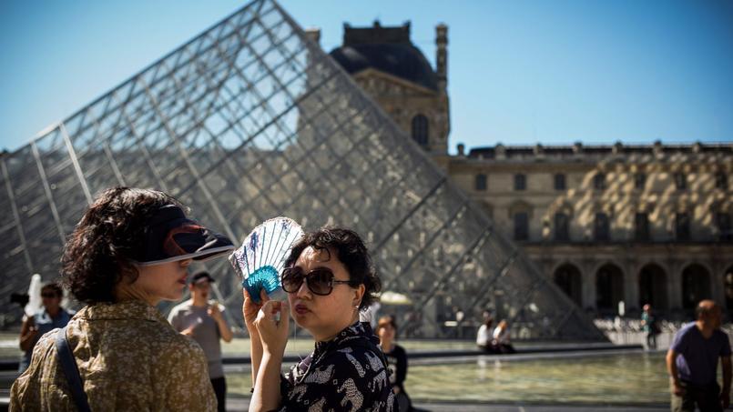 Des touristes devant le musée du Louvre à Paris, au mois d'août 2016.