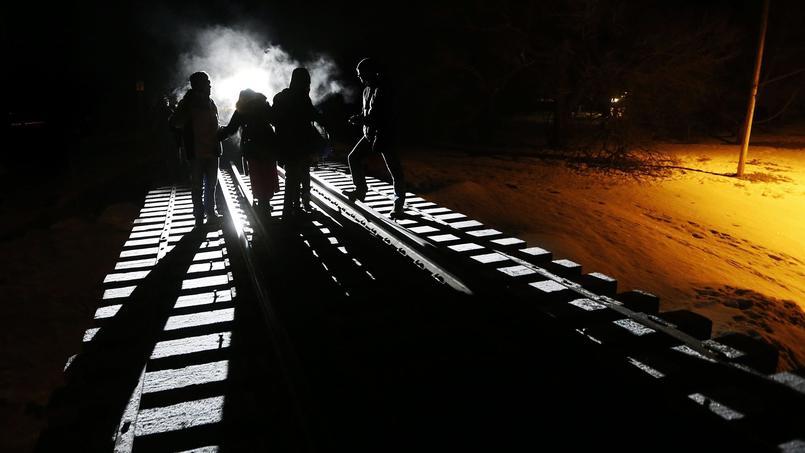 Des migrants somaliens traversent la frontière entre les États-Unis et le Canada en suivant une ligne de chemin de fer, à Emerson, dans la province canadienne du Manitoba, dimanche 26 février.