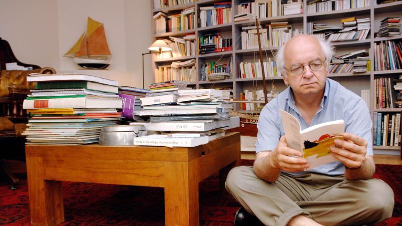 L'écrivain Erik Orsenna consultant un ouvrage à son domicile parisien.