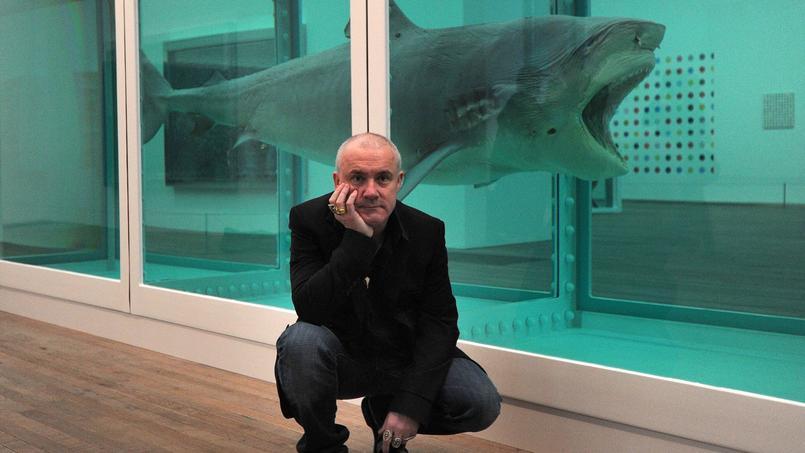 L'artiste britannique Damien Hirst pose devant son travail de 1991 «L'Impossibilité physique de la mort dans l'esprit de quelqu'un vivant» lors de l'ouverture de son exposition à la Tate Modern à Londres le 2 avril 2012 .