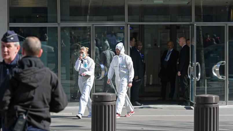 Deux agents de la police scientifique quittent les locaux du FMI, avenue d'Iéna, à Paris, jeudi après-midi.