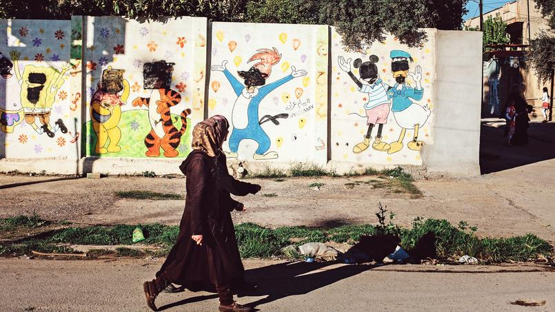 Signe encore visible de la présence de l'État islamique, des visages de personnages de dessins animés peints sur les murs d'une crèche du quartier de Mouthanna sont toujours recouverts de peinture noire.