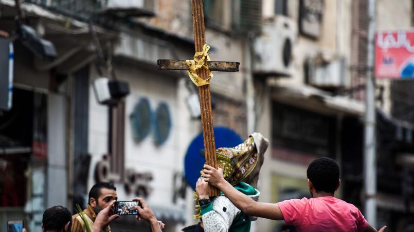 Des égyptiens brandissent une croix, devant l'église d'Alexandrie touchée par une explosion, dimanche.