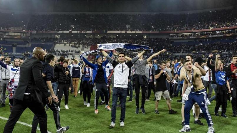 Les supporters lyonnais ont trouvé refuge sur le terrain après les jets de projectiles venus des tribunes supérieures.