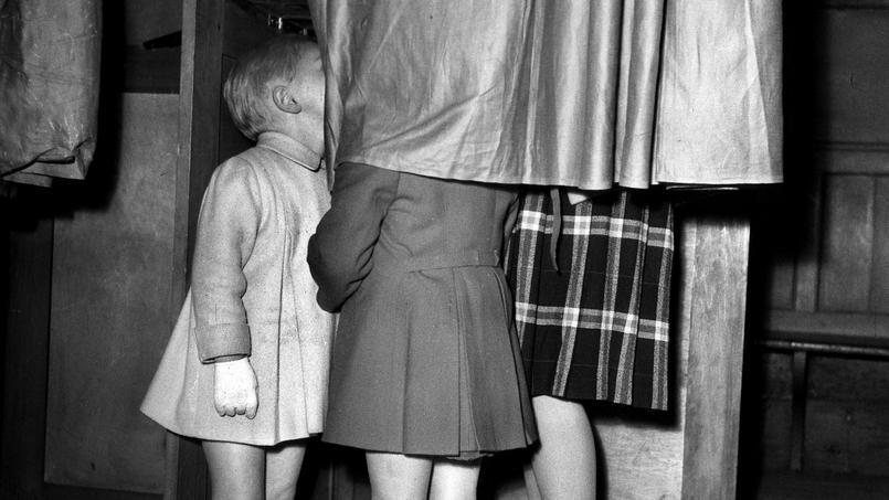 Au bureau de vote, les enfants accompagnent leur mère dans l'isoloir, 1946.