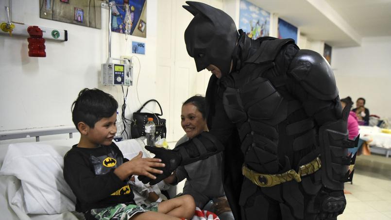 Pablo, sept ans, vêtu de son pyjama Batman, serre la main de son super-héros.