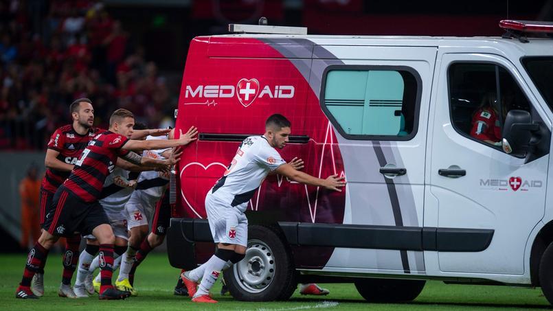 Des footballeurs poussent une ambulance tombée en panne sur le terrain — Brésil
