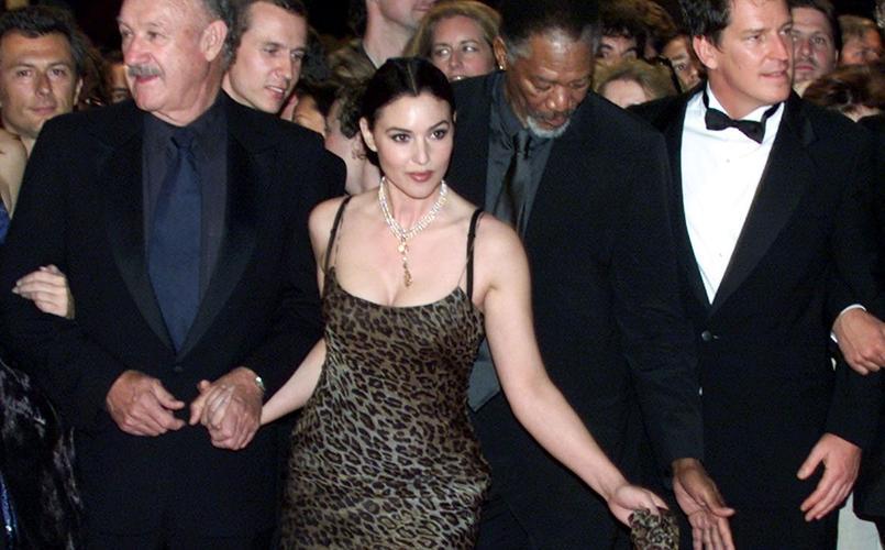 Monica Bellucci pose sur le tapis rouge avec les acteurs Gene Hackman (à gauche), Morgan Freeman (derrière) et le réalisateur Stephen Hopkins (à droite).
