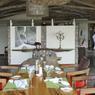 La salle à manger de ChemChem Safari Lodge ornée des photos animalières de Michaël Poliza d 'un côté et ouverte sur la savane de l'autre.