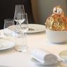 Le service de table est signé Raynaud, célèbre manufacture de porcelaine de Limoges, tandis que la décoration de la table provient des cristalleries Baccarat.