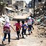 SUR LES CHEMINS DE DAMAS.Sans les ruines et les bâtiments dévastés qui les entourent, on pourrait croire que tout va bien pour ces petits Syriens en route vers l'école. Et que la vie suit ici son cours normal dans ce qui fut l'un des plus beaux pays du Levant. Mais, dans la ville rebelle de Jobar, dans la banlieue est de Damas, la capitale syrienne, les enfants savent désormais que leur vie ne tient qu'à un fil. Parfois, derrière les murs écroulés des immeubles, des tireurs embusqués sont postés, prêts à faire feu. Alors ils courent, aussi vite qu'ils le peuvent. Ils ont fini par s'y habituer. Comme aux bombardements et aux tirs d'artillerie. Depuis le début du conflit en 2011, des dizaines de milliers d'enfants n'auront connu que la guerre et ses horreurs.