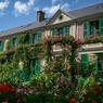 Vue sur la célèbre façade crépie de rose de la maison de Monet à Giverny. Au premier plan, les massifs de géraniums vermillon, conformes à ce qu'ils étaient du temps de l'artiste, sont en parfaite harmonie avec le vert des volets auquel se mêle le feuillage des rosiers grimpants.
