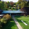Construit en 2000, ce bâtiment caractéristique de l'Arboretum accueille les visiteurs avec sa boutique, son salon de thé et le kiosque de la pépinière de l'Arboretum (à gauche). Cette dernière produit chaque année plusieurs centaines d'espèces et variétés, pour majorité élevées entièrement sur le site et dont certaines servent au renouvellement des collections.