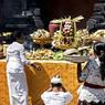 Scène de la vie quotidienne à Ubud, les bras chargés de paniers, remplis de fleurs, de fruits, d'encens et de riz, les pélerins déposent ces offrandes au pied d'un temple.