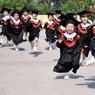 JEUNES DIPLÔMÉS. Des enfants en robes traditionnelles d'écoliers courent avec un large sourire aux lèvres durant la cérémonie de remise des diplômes de leur garderie, le 20 juin à Handan, province d'Hebei. Vive les vacances !