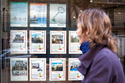 Femme regardant la vitrine d'une agence immobilière. Crédits photo: ARNAUD ROBIN / Le Figaro Magazine