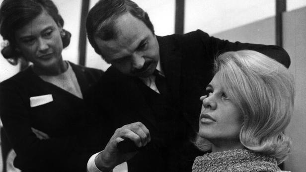 Le coiffeur Jacques Dessange coiffant le mannequin Deborah lors d'un salon en Ecosse le 12 octobre 1965.