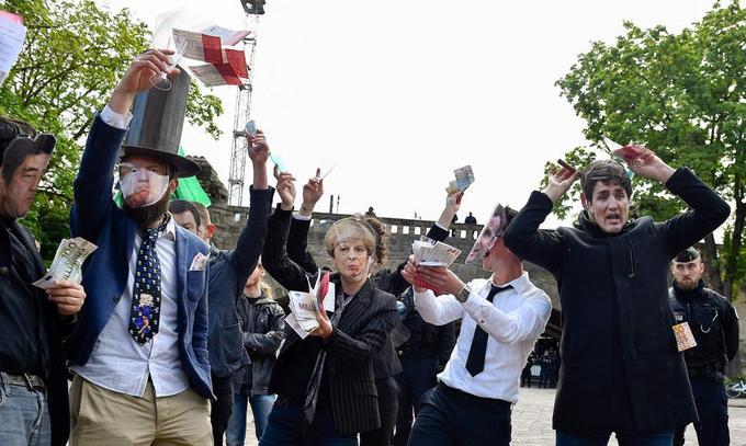Des hommes et des femmes en costume ou manteau noir, portant des masques représentant les visages des dirigeants du G7.
