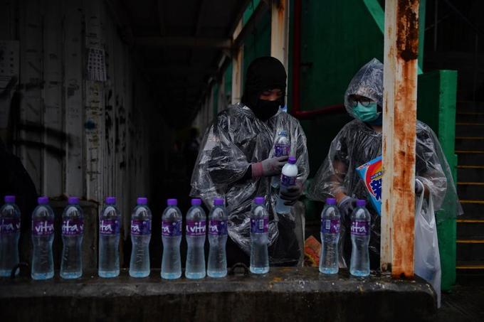 Des manifestants mélangent du savon et de l'eau dans des bouteilles, à Hongkong, le 25 août.