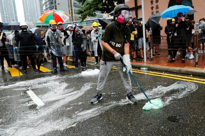 Un manifestant répand du liquide vaisselle sur le sol pour compliquer l'intervention des forces de l'ordre