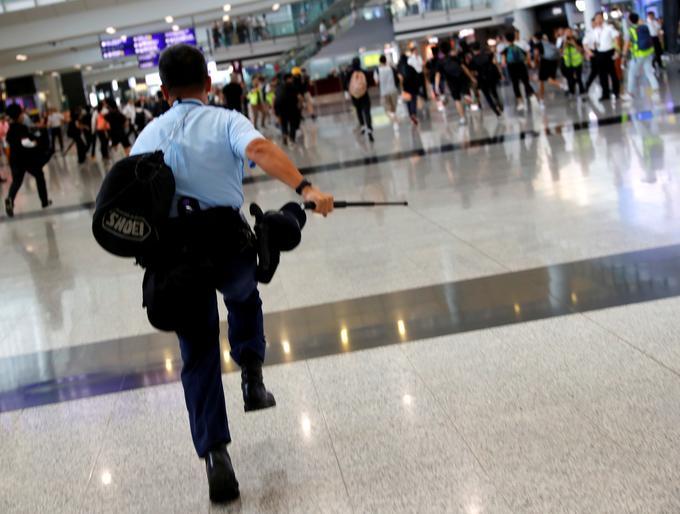 Un policier poursuit des manifestants à l'aéroport de Hongkong ce dimanche.