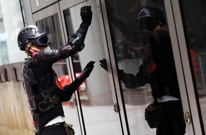 Un manifestant tente de briser une porte vitrée de l'aéroport de Hongkong.