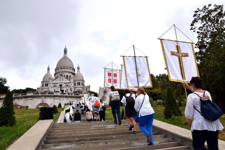 70 bannières de Saints se préparent pour former une haie d'honneur dans la montée jusqu'au Sacré-Cœur