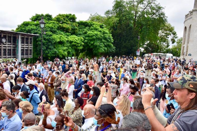 Dans la foule autour du Sacré-Cœur, certains chrétiens ne portent pas de masque. D'autres le portent sous le nez ou sous le menton.