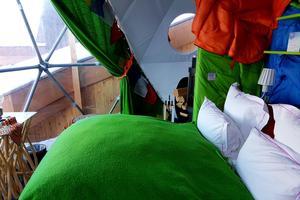 Patchwork de toiles de tentes aux couleurs chamarrées pour la chambre double nichée dans l'igloo-pod.