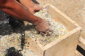 Les bouteilles, matière première dans la fabrication du béton, sont broyées en petites billes et transportées sur le chantier dans d'énormes sacs.